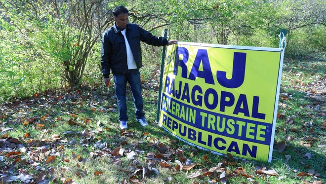 Newly elected Colerain Township trustee Raj Rajagopal takes down one of his campaign signs on Blue Rock Road the day after the election.
