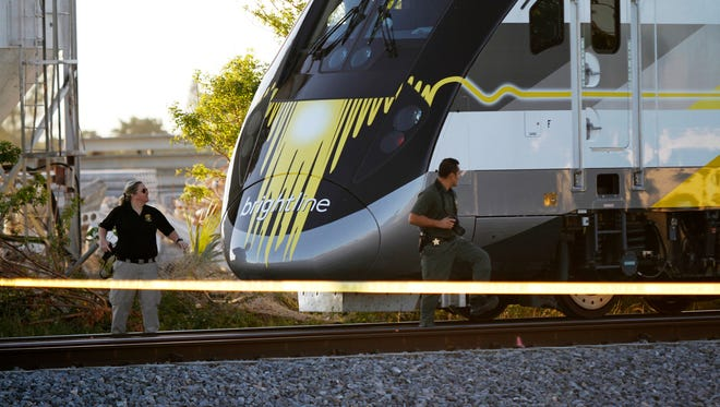 Crime scene investigators photograph a Brightline train in Broward County after it hit and killed a person Wednesday, Nov. 1, 2017, in Deerfield Beach.