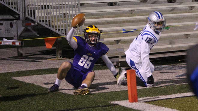 Stephen Halusan (left) celebrates after catching a touchdown in the corner of the end zone during the first quarter against Whitefish Bay on Nov. 10.