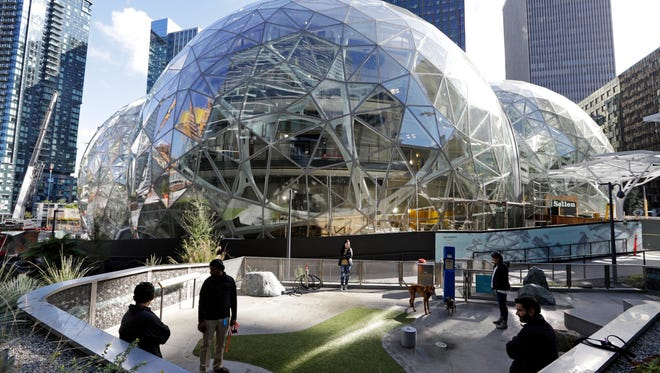 In this photo taken Wednesday, Oct. 11, 2017, large spheres take shape in front of an existing Amazon building and adjacent to a small dog park provided by the company, in Seattle.