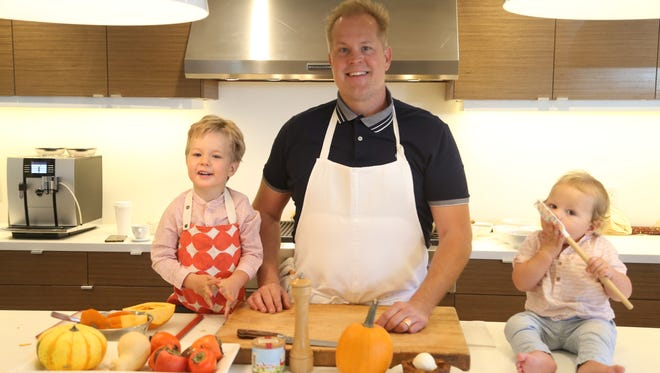 Chef Aaron Chamberlin (center) cooks with his sons Arturo, 3, (L) and Schaefer, 9 months, in Phoenix, Ariz. on November 7, 2017.
