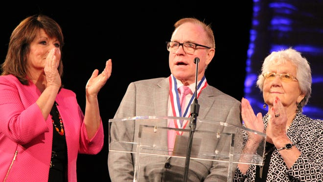 Troy Burns speaks at the induction into the Southern Gospel Music Association Hall of Fame. Joining him are Tammy Burns, at left, and Mildred Burns.