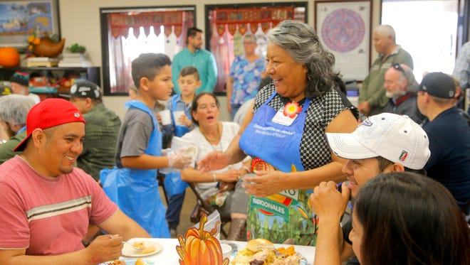 OMNI Resource Center Staff Ricarda Rodriguez laughs with Hector Alacon during the center's Thanksgiving meal.