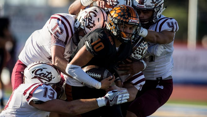 Mercedes' Matthew Ledesma is tackled by Calallen defenders during their 5A Division II area round playoff game Friday, Nov. 24, 2017, at Javelina Stadium in Kingsville.