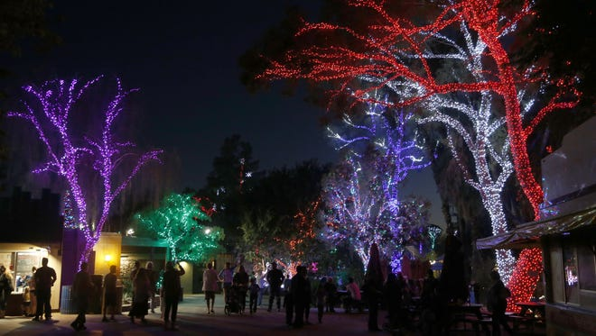 People walk through and look at the holiday lights during ZooLights at the Phoenix Zoo on Friday, Nov. 24, 2017 in Phoenix, Ariz.