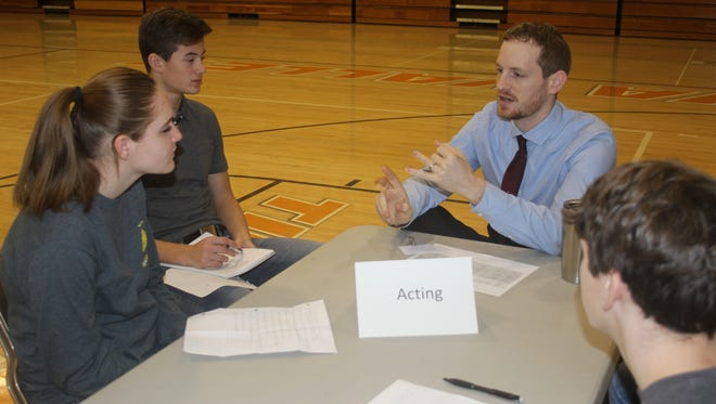 Baylee Anderson, Tristan Stubblefield, and Kyle Schlak listen to Keegan Christopher, Artistic Associate with Old Creamery Theatre Co.
