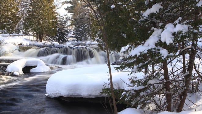 The Bond Falls make for a gorgeous backdrop during a winter snowshoe hike through Michigan's Upper Peninsula.