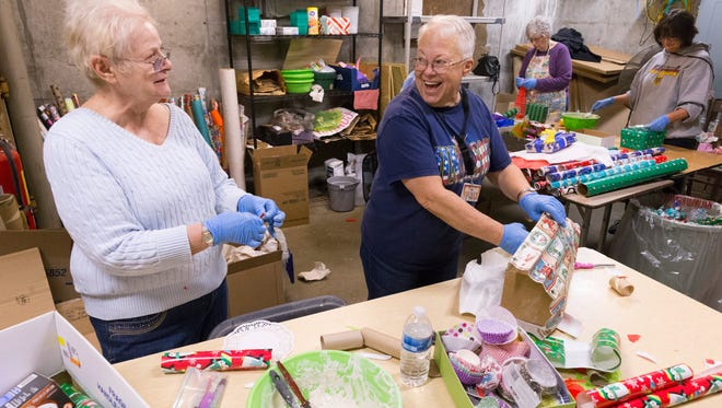 Volunteers Carol Weaver (left) and Jan Nosse share a laugh while wrapping boxes that will be used for enrichment gifts  at the Milwaukee County Zoo.