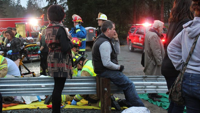 In this photo provided by Daniella Fenelon, first responders work at the scene of an Amtrak train that derailed in DuPont, south of Seattle on Monday, Dec. 18, 2017.