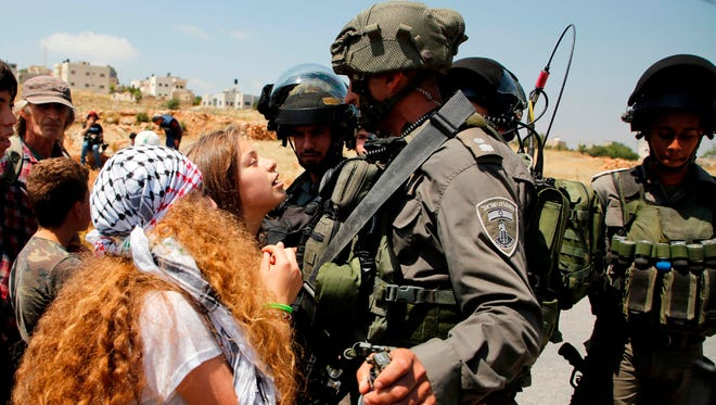 This file photo taken on May 12, 2017 shows 17-year-old Ahed Tamimi, center, protesting before Israeli forces in the West Bank village of Nabi Saleh, north of Ramallah.