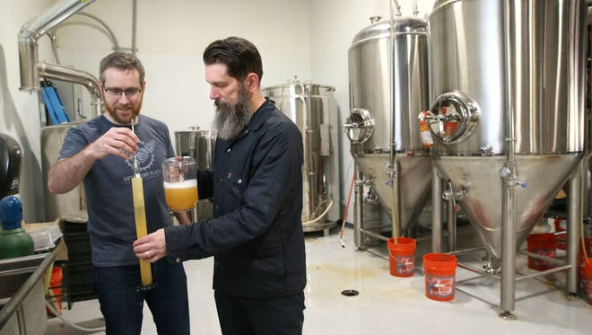 Joe Yeado (left) founder, and Corey Blodgett, brewmaster, test the gravity of a beer at  Gathering Place Brewing Company, 811 E. Vienna Ave.