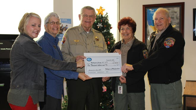 Community Relations Director Hope Patterson and Executive Director Terri Deal of The Villages of Murfreesboro present a $1,000 check to Sheriff Mike Fitzhugh and SCAN coordinator's E.T. and Clarence Guice. The funds were raised through a silent auction of Christmas trees and wreaths at the Villages.