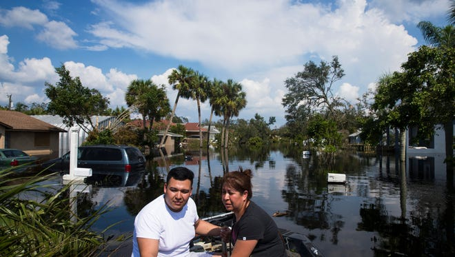 Juan Cardona and his mother Juana Ramirez sit on the bow of a boat as they are ferried across flood waters to check on their home on Saunders Avenue in Bonita Springs on Thursday, Sept. 14, 2017, four days after Hurricane Irma.