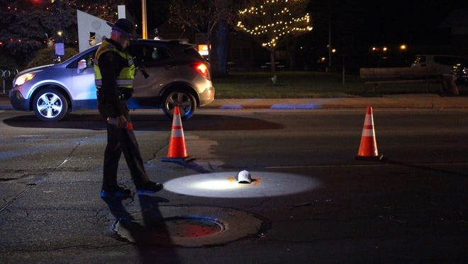 An Ohio Highway Patrol trooper shines a light on a baseball cap left in the road after a hit-skip between a truck and a pedestrian in Lexington on Dec. 21.
