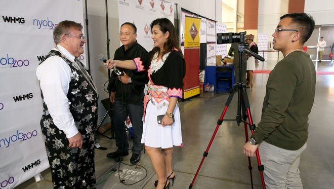 """Dawn Yang (center right), the general manager of a TV show dedicated to the Hmong American community called """"Nyob Zoo Milwaukee"""" on Channel 38, and her husband, Thay Yang, CEO of WHMG Media (center left), interview Don Cohen, vice president of Landmark Credit Union, at the Hmong New Year celebration held at the State Fair Park Expo Center.  The credit union is a sponsor of the event.  At right is videographer Soon Loh Vue."""