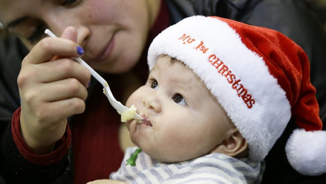 Five-month-old Liam Rico, of Phoenix, enjoys a meal during the annual Salvation Army Christmas dinner at the Phoenix Convention Center on Dec. 25, 2017 in Phoenix.