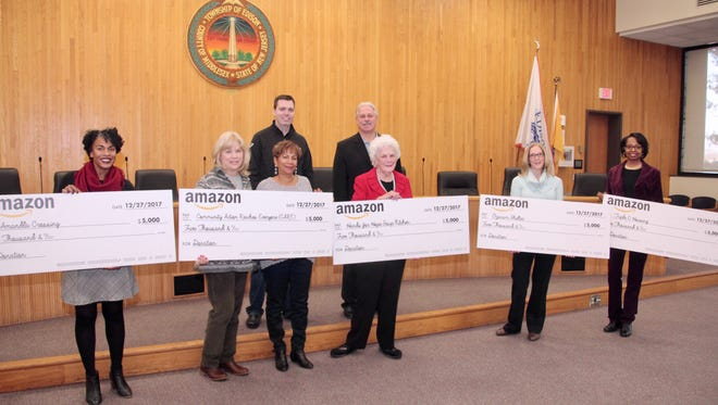 Amazon leaders joined with Edison Mayor Tom Lankey at the municipal complex Wednesday to present $5,000 checks to five local charities that serve township residents.