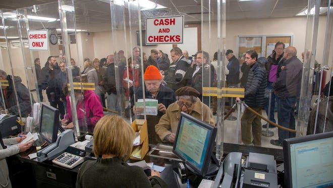 This Dec. 26, 2017, photo shows people lined up in the Hempstead, N.Y. tax receiver's office to prepay their property taxes before the end of 2017, hoping for one last chance to take advantage of current tax deductions before they disappear at the start of 2018.