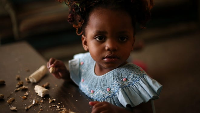 Madede Mambo, 2, eats cassava root in the family's living room in Tallahassee, just a month after they were relocated as refugees, fleeing the Democratic Republic of the Congo.