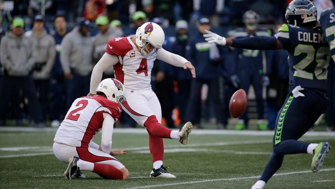 Arizona Cardinals kicker Phil Dawson, right kicks a field goal against the Seattle Seahawks in the first half of an NFL football game, Sunday, Dec. 31, 2017, in Seattle. (AP Photo/John Froschauer)