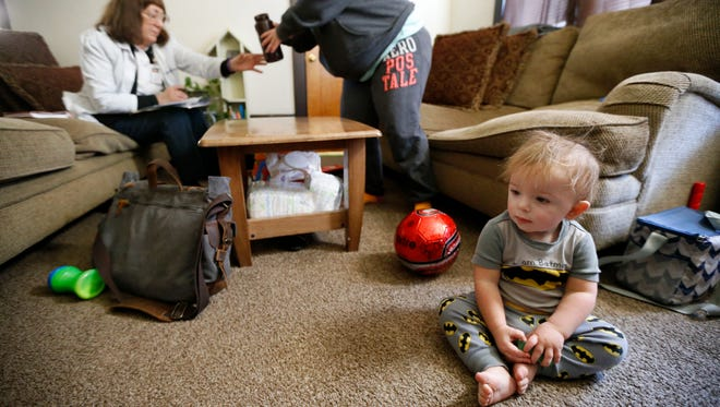 Hudson, 17 months, plays with his toys while his mother, Mariah Roseberry, answers questions about lead poisoning risk factors in her home in the Price Hill neighborhood of Cincinnati on Friday, Jan. 5, 2018. Hudson tested at a blood lead level of 5.4. No level of lead is safe, but medical professionals consider anything higher than 5 to be lead poisoning.