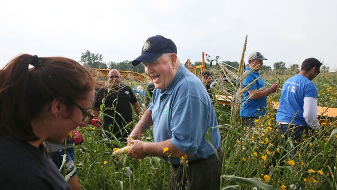 Ag Secretary Sonny Perdue shucks an ear of corn as he talks with volunteers and staff picking a field of sweet corn by hand during a stop on his RV tour in August.