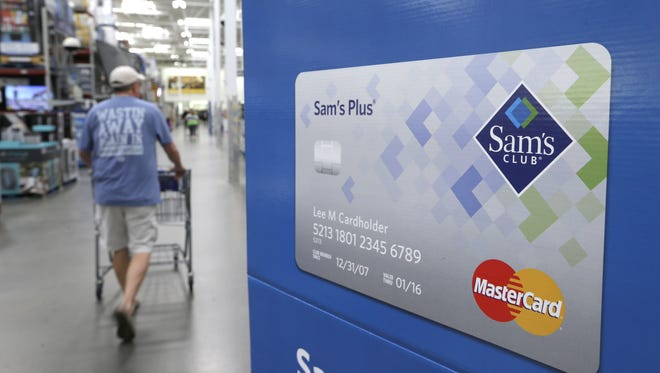 A customer walks past a sign promoting the Sam's Club Mastercard credit card in Bentonville, Ark.