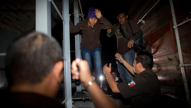 Immigration officials remove Central American migrants from a northbound freight train during a raid by federal police in San Ramon, Mexico, just after midnight on the morning Aug. 29, 2014.