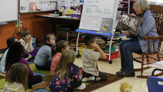 "Paula Steger reads ""Radiant Child"" to the first grade class. FIT Oshkosh took its Library on Wheels into Gail Bertram's first grade class at Oaklawn Elementary school, January 30, 2018.  The students were read two books and then did a artwork project based on one of the books.