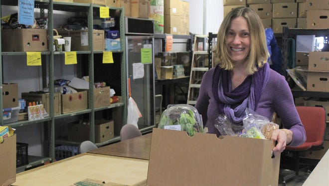 Beacon of Hope Director Jessi Koontz carries a box loaded with food inside the nonprofit's pantry. Each Monday, the Beacon of Hope distributes staples to roughly 120 local families.