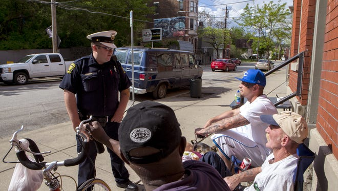 Quality of Life of Metro Wednesday April 30, 2014: Cincinnati Police Officer Richard Longworth, left talks with residents Hank Morgan (cq) son and father Geno Gribbins (cq) and Randy Gribbins (cq) as Officer Longworth walks the street as part of the Quality of Life foot patrol Wednesday April 30, 2014 in Lower Price Hill. Hank Morgan is a 6 year resident of Lower Price Hill. Geno Gribbins has lived in lower Price Hill for 5 years. Randy Gribbins has lived in Lower Price Hill still 1953. The Enquirer/ Joseph Fuqua II
