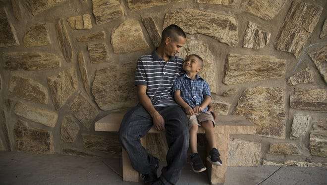 Jesus Berrones sits with his 5-year-old son Jayden at Shadow Rock Shadow Rock United Church of Christ where he is in sanctuary on Feb. 11, 2018 in Phoenix. ICE had planned to deport Berrones on Monday, February 12. Berrones administers his son's chemotherapy drugs daily because his wife who is pregnant can't be around when the bottle is open.