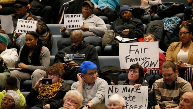 Attendees in opposition of the FC Cincinnati stadium West End location display signs during a Board of Education weekly meeting at the Cincinnati Board of Education in the Avondale neighborhood of Cincinnati on Monday, Feb. 12, 2018.
