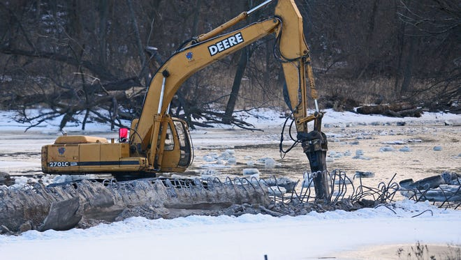 An MMSD contractor uses an excavator arm to break apart a section of the Estabrook Park dam on the south shore of the Milwaukee River.