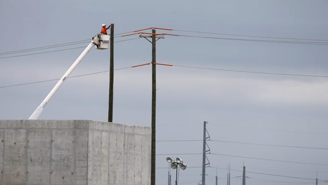 A worker is shown near a utility pole at unit two of the V.C. Summer Nuclear Station near Jenkinsville, S.C., during a media tour of the facility Wednesday, Sept. 21, 2016.  SCE&G is seeking a 3.1 percent residential raise that would be the largest single rate increase since the utility began charging its 700,000 customers for the reactors' construction. The hike, which would take effect at the end of November if approved, would be the ninth such increase to pay for the $14 billion reactors since 2009. (AP Photo/Chuck Burton)
