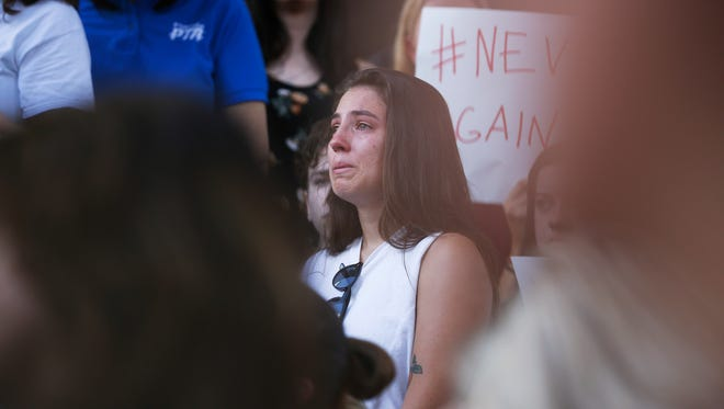 A young woman cries during a protest against guns on the steps of the Broward County Federal courthouse in Fort Lauderdale, Fla., on Saturday, Feb. 17, 2018. Nikolas Cruz, a former student, is charged with killing 17 people at Marjory Stoneman Douglas High School in Parkland, Fla., on Wednesday.