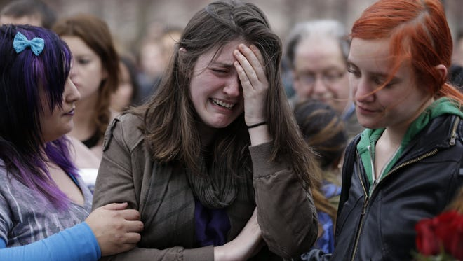 Emma MacDonald, 21, center, cries during a vigil for the victims of the Boston Marathon explosions at Boston Common, Tuesday, April 16, 2013.