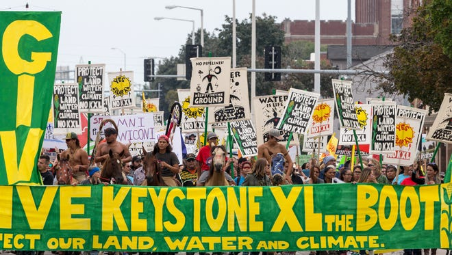 Demonstrators against the Keystone XL pipeline march in Lincoln, Neb. Opponents of the proposed oil pipeline from Canada are asking a federal judge to force the U.S. government to turn over emails and other documents related to President Donald Trump's approval of the project.