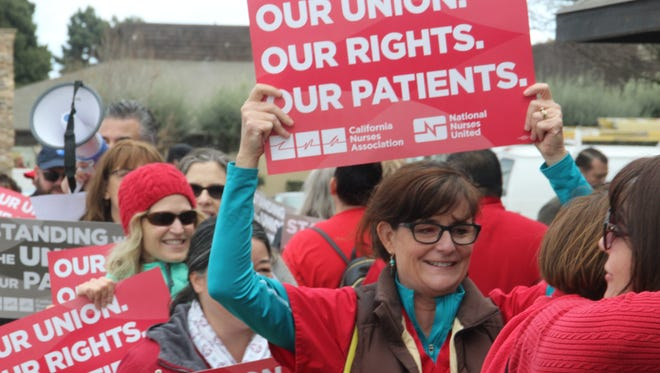 Liz Dayton, a registered nurse at Salinas Valley Memorial Healthcare for 25 years, holds up a sign alongside other nurses during a rally over a case on union membership the U.S. Supreme Court will hear next week.