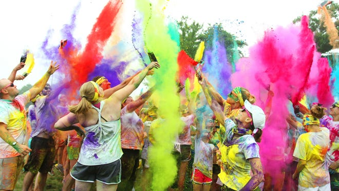 Participants at the Kolor for Kids FunFest in 2014 throw color packets in the air at the end of their run at Grand Rapids Lions Park.