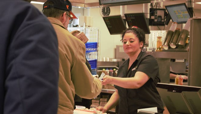 """Trista Fulton hands out cake to Burger King customers Tuesday for its reopening. The Burger King franchise completely redid its dining room and rearranged its kitchen, too. Fulton has been working at the Burger King, 1278 Mount Vernon Ave., for 21 years and that she """"loves"""" the renovations, she said."""