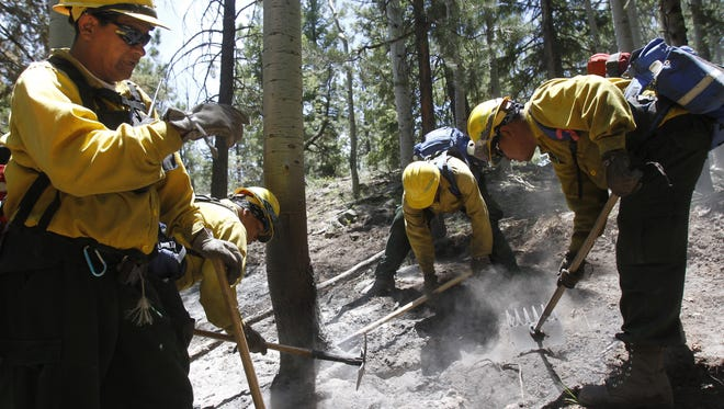 Navajo Scouts crew boss Irvin Begay, right, gives instructions to his crew June 20, 2014, as they take control of the Assayii Lake Fire in the Sand Spring area on Ch'ooshgai Mountain.