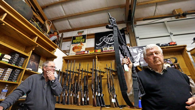 Tom Wallitner holds up a Mossberg 715T .22-caliber semi-automatic rifle during an auction at Johnny's Auction House, where the company handles gun sales for a half dozen police departments and the Lewis County Sheriff's Office, in Rochester. The Washington state Legislature ended the session without passing a bill that would allow the State Patrol to destroy firearms confiscated during criminal investigations.