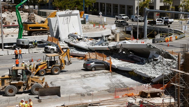 Crushed cars are shown under a section of a collapsed pedestrian bridge on March 16, 2018 near Florida International University in the Miami area.