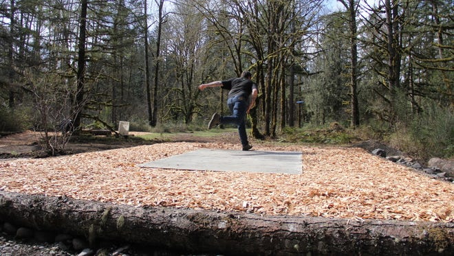 Matthew Coll throws a disc off the renovated tee box on hole No. 2 at the refurbished disc golf course at Camp Taloali in Stayton.