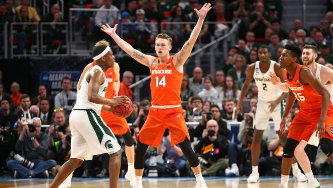 Former Grinnell College player Braedon Bayer, 14, blocks a Michigan State player for the Syracuse Orange during action in the NCAA basketball tournament in Detroit.