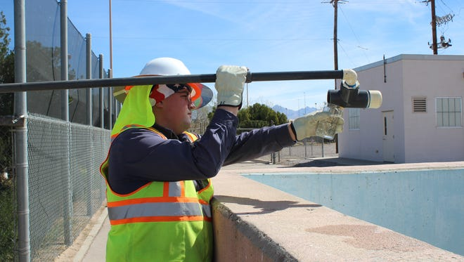 Las Cruces Utilities intern Bryan Eakins takes a sample at the the Jacob A. Hands Wastewater Treatment Facility