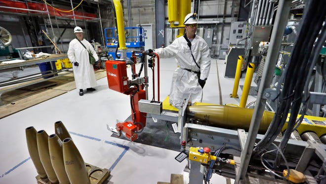 FILE - In this Jan. 29, 2015, file photo, ordnance technicians use machines to process inert simulated chemical munitions used for training at the Pueblo Chemical Depot, east of Pueblo, in southern Colorado. The costly plant in Colorado that destroys U.S. chemical weapons without incinerating them is over budget, behind schedule and bedeviled by troubles that could worsen the danger to workers. But when the Army said this month it wants to spend millions more installing older technology to help the beleaguered plant and reduce worker risk, public reaction was more acceptance than anger. (AP Photo/Brennan Linsley, File)