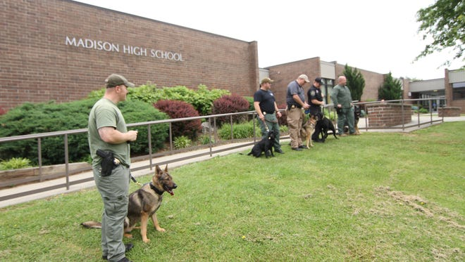 K-9 officers stand outside Madison High School following a bomb threat that closed the campus in May 2016.