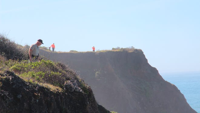 Deputy Bill Holcomb looks down the cliff near the crash site near Mendocino, Calif., as search and rescue volunteers scour the area behind him on Thursday, March 29, 2018, and resume looking for three children, still missing after their parent's SUV plunged into the ocean Monday. Investigators have yet to determine the cause of the crash. (Kale Williams/The Oregonian via AP)